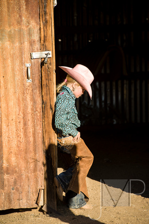 _small child in cowgirl clothes against a barn door